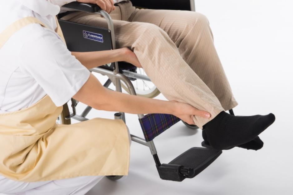 老人を車椅子に乗せている介護士