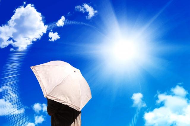 太陽の下で日傘をさす人